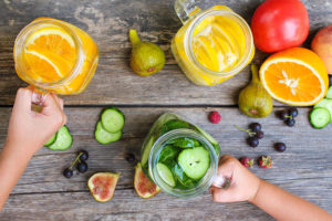 Children's hands take drinks with fruit and vegetables © Adobe Stock